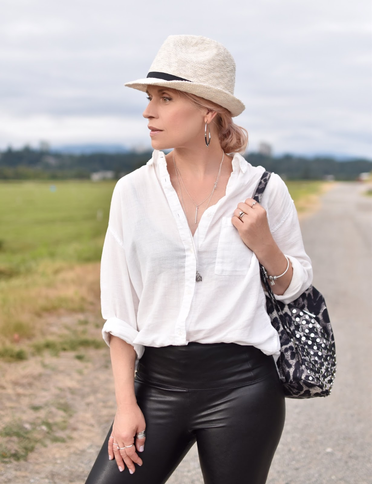 Monika Faulkner personal style inspiration - black vegan leather leggings, oversized white shirt, straw fedora, leopard-patterned backpack