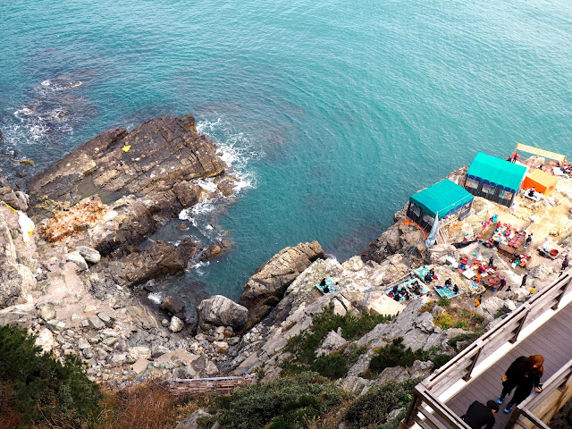 Rocks along the coast of Yeongdo Island, with seafood tents, taken from Yeongdo Lighthouse, Taejongdae Park, Busan, South Korea