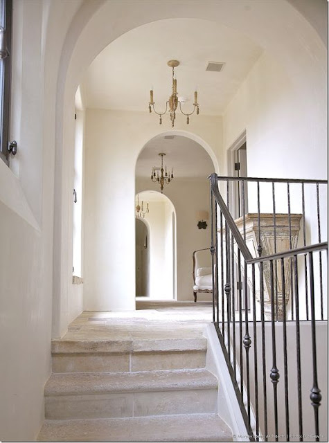 Limestone stairway and wrought iron railing leading to archway and chandelier