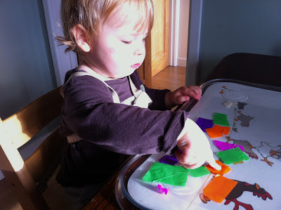 toddler is placing bits of tissue paper on contact