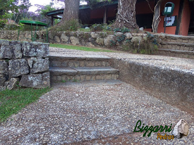 Escada de pedra folheta nesse tom de cor de pedra cinza escuro sendo uma pedra de granito apicoada. Escada de pedra com os muros de pedra e os caminhos com pedregulho do rio.