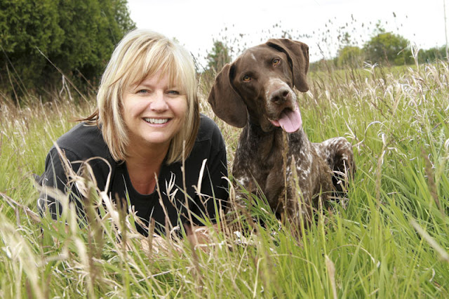 A woman and her German Shorthaired Pointer relaxing in a field