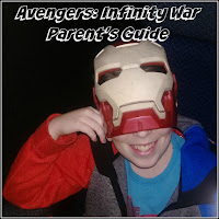 Boy seated in cinema wearing Iron Man mask.