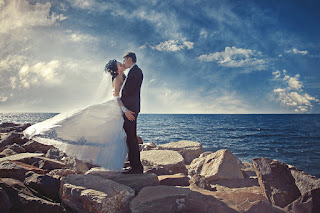 Bride-and-groom-kissing-near-sea-rocks-with-beautiful-sky-HD-image.jpg