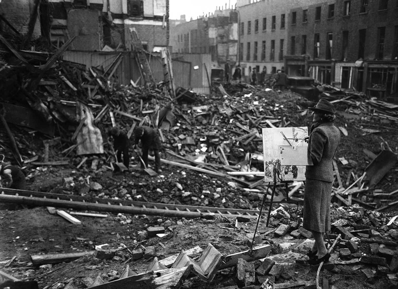 The artist Ethel Gabain, newly appointed by the Ministry of Information to make historical war pictures, at work among bombed ruins in the East End of London on November 28, 1940.