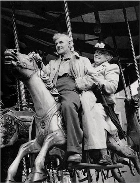 An elderly couple rides the Merry Go Round. 1950s.