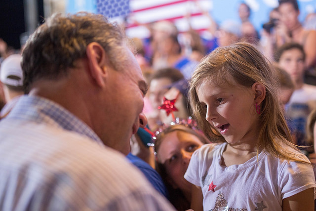 Vice-Presidential candidate Tim Kaine listens to a little white girl in attendece at a campaign rally