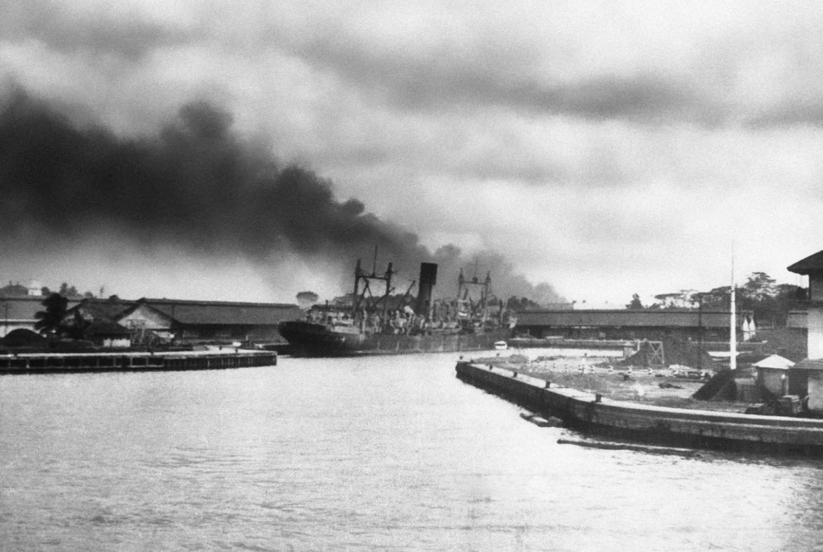 A large freighter settles slowly after being hit by Japanese bombs alongside of one of Singapore's docks on February 12, 1942. Smoke from other struck objectives billows over the waterfront in this photo by C. Yates McDaniel, Associated Press correspondent, who was among the last to leave the besieged port on February 12. The next day his ship was bombed and he reached safety after further harrowing experience.