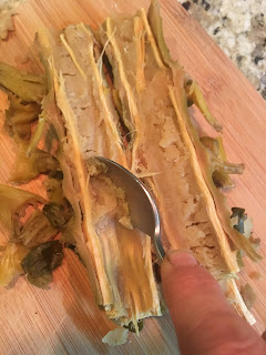 Photo of the author scooping the core from the cooked Brussels stalk with a spoon. https://trimazing.com/