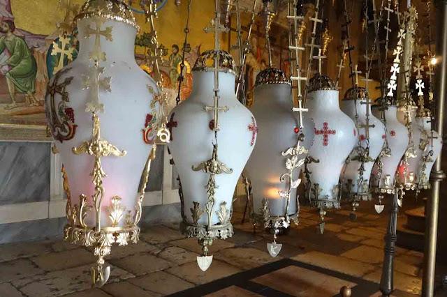 A l'entrée de la Basilique, les huit lampes suspendues au-dessus de la pierre de l'onction