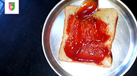 image of spreading tomato sauce on bread