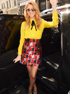 Celine Dion in a yellow ruffle shirt with a black neck tie and a Gucci red blue and purple pattern mini skirt