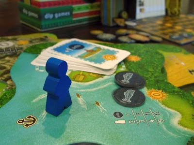 Blue player board game meeple and Altiplano shoreline location board with fish and canoes