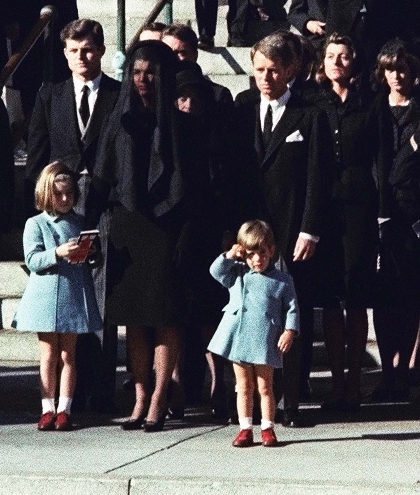 John F. Kennedy Jr., who turns three today, salutes as the casket of his father, the late President John F. Kennedy. Widow Jacqueline Kennedy, center, and daughter Caroline Kennedy are accompanied by the late president's brothers Sen. Edward Kennedy, left, and Attorney General Robert Kennedy.