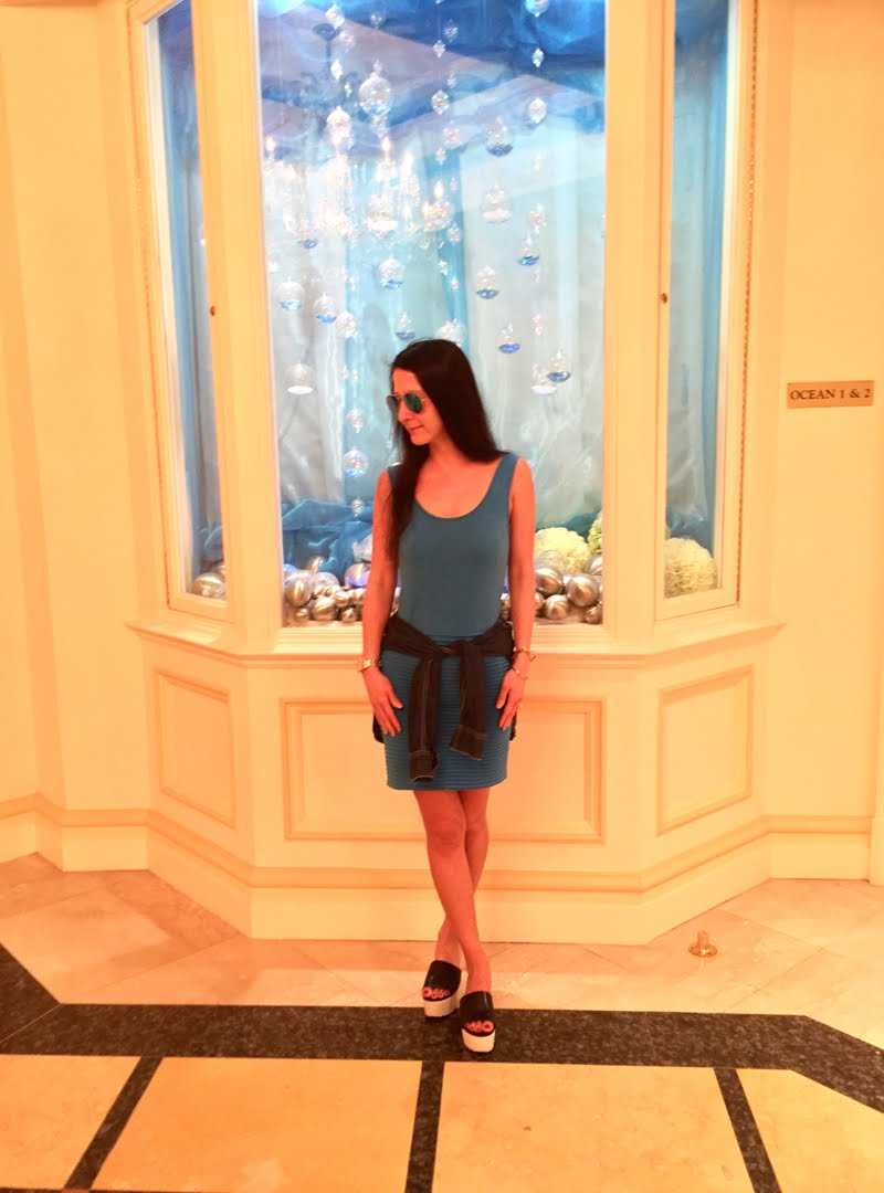 Blue and Jean Outfit at Palm Beach in front of display.
