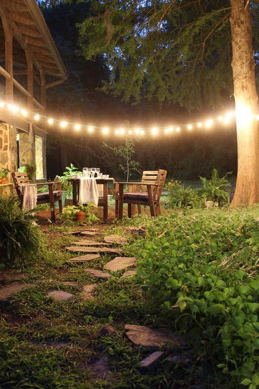 Nighttime alfresco garden dining under string lights