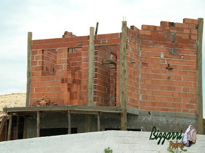 Detalhe da alvenaria de tijolo baiano nos pilares de madeira de eucalipto tratado na construção da sala de estar com a suíte superior com a marquise de concreto e os pilares de madeira.