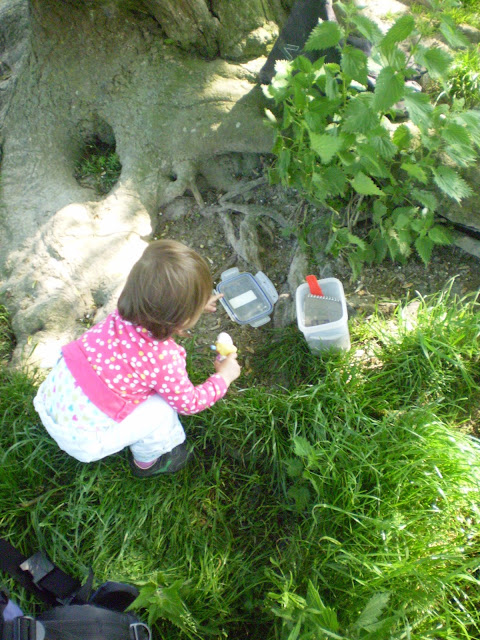 Daughter crouched down with a geocache next to a tree