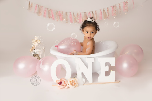 """Little girl sits in a small white bathtub surrounded by pale pink balloons, soap bubbles, and flowers. Three white wooden signs with the letters """"O"""", """"N"""", """"E"""" lean against the bathtub just below her"""