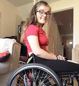 A teenage girl wearing glasses with long light brown hair. she is wearing a red top and black leggings and is sat in a wheelchair.