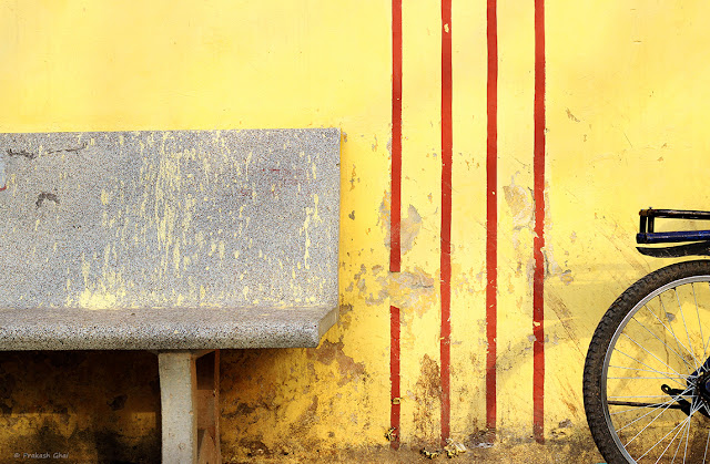 A Minimalist Photo of a Bicycle parked near a bench against a yellow wall