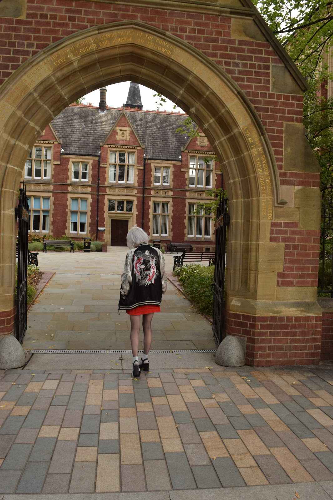 silver haired girl under archway in Leeds university wearing souvenir jacket, heels and red dress