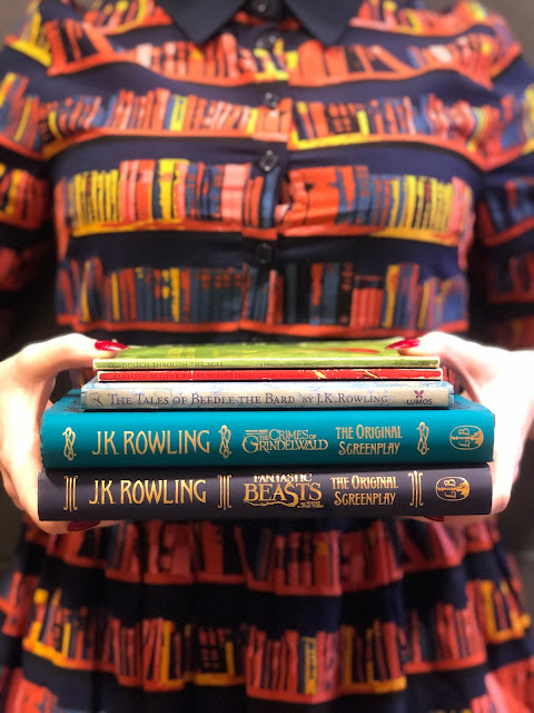 AJ holding Harry Potter and Fantastic Beasts books while wearing a library print dress from Joanie Clothing