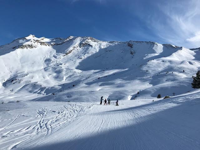 Paisaje montañoso nevado con esquiadores a lo lejos