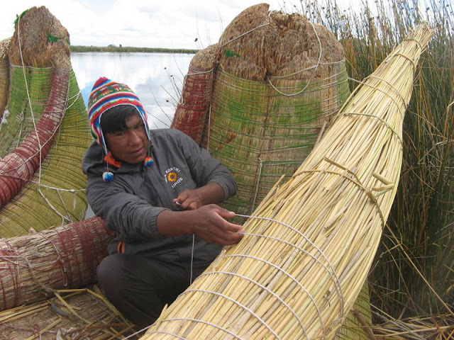 man mending straw boat on Uros Islands, Peru