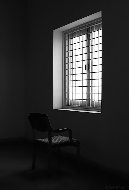 A Black and White Minimal Art Photo of an Empty Chair against an Open Window with light coming through it. Shot taken at Jawahar Kala Kendra, Jaipur - India