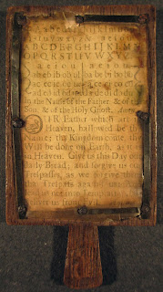 A primer with a page of text on a wooden frame.