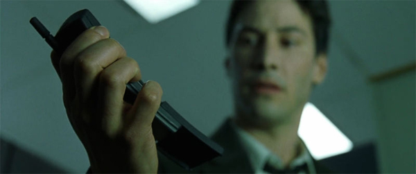still from 'The Matrix' of Keanu Reeves holding and looking at a Nokia banana phone