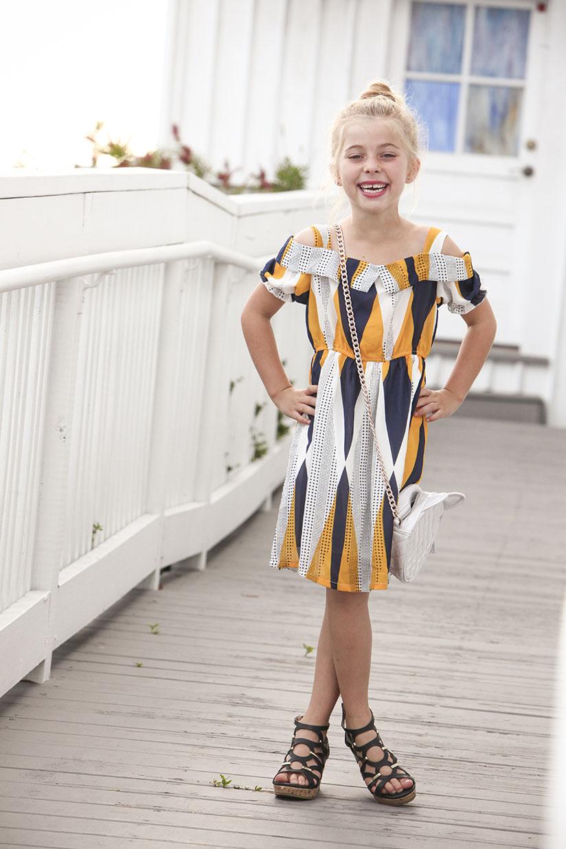 Little girl smiling in trendy dress