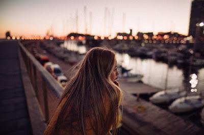 Chica mirando el puerto al atardecer