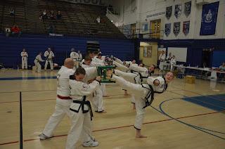 Four martial arts girls using teamwork to break boards