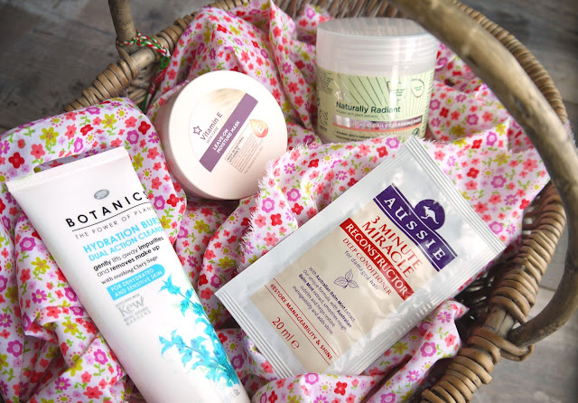 a wicker basket lined with pink floral fabric, and filled with tubs of cleansers and skincare