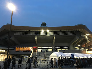 "The Budokan lit up at night with the golden ""onion"" dome visible on top"