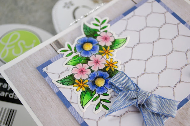 Layered farmhouse / country style prints, and gorgeous denim look ribbon create an amazing backdrop for the stamped flower image from Fun Stampers Journey's Flower Shower stamp set - colored with Journey Color Burst colored pencils.