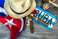 A few things juxtaposed together on a wood background, Cuban flag  three Cuban cigars, a Cuban fedora hat, cuban maracas