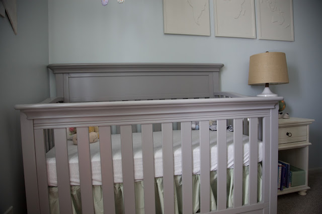A travel and adventure-inspired gender neutral nursery with pops of pale gray, white, blue, and green.