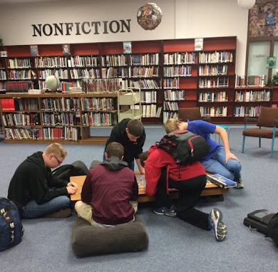 photo of boys working on project in library