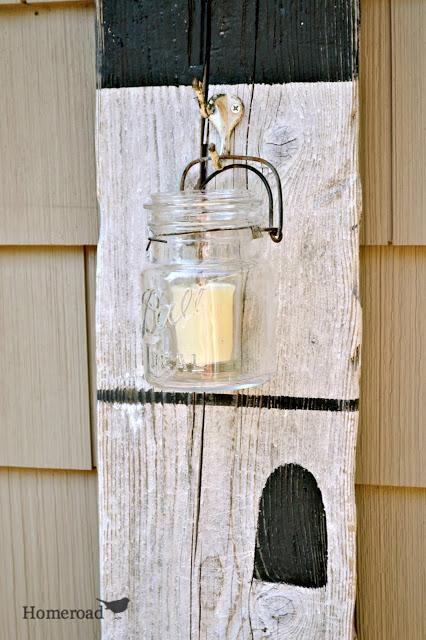 Large driftwood plank with hanging mason jar candle.