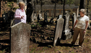 Two people taking in a graveyard