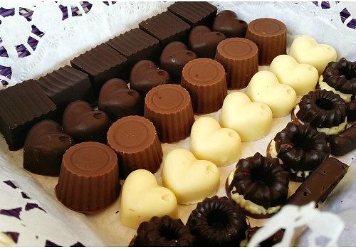 Unos bombones de chocolate blanco , con leche y puro. Formas varias