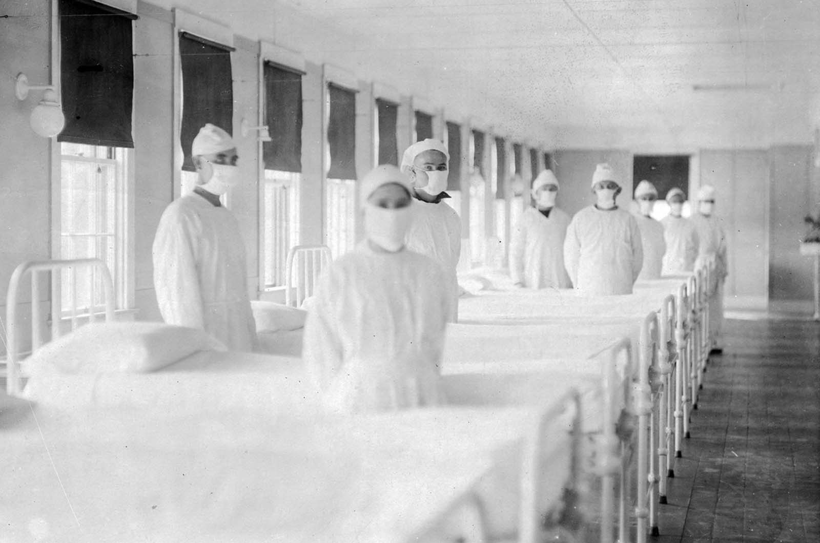 Corpsmen in caps and gowns are ready to attend patients in the influenza ward of a U.S. Navy hospital, in Mare Island, California, on December 10, 1918.