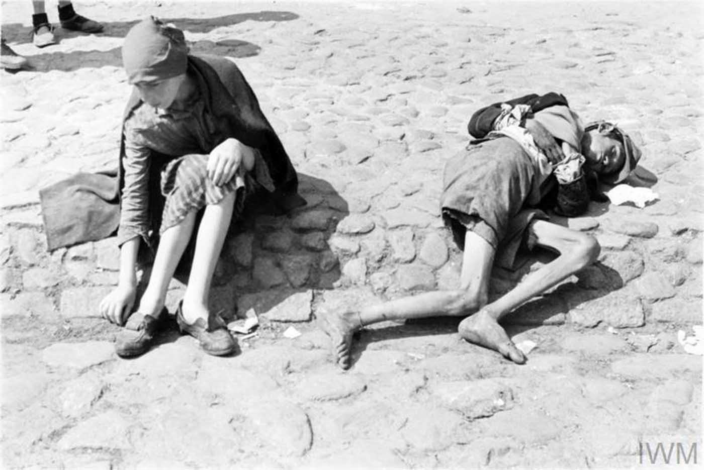 Two emaciated children, one of them asleep or unconscious, begging on the street of the ghetto.