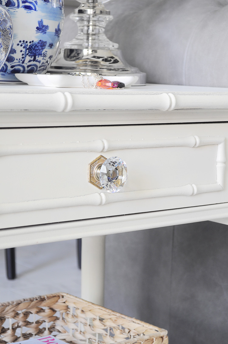 A crystal cabinet knob gives a chic and glam look to an antique bamboo end table revamp.