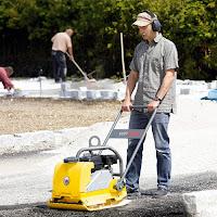 Bir yola dökülen asfaltı bir kompaktör ile sıkıştıran bir işçi