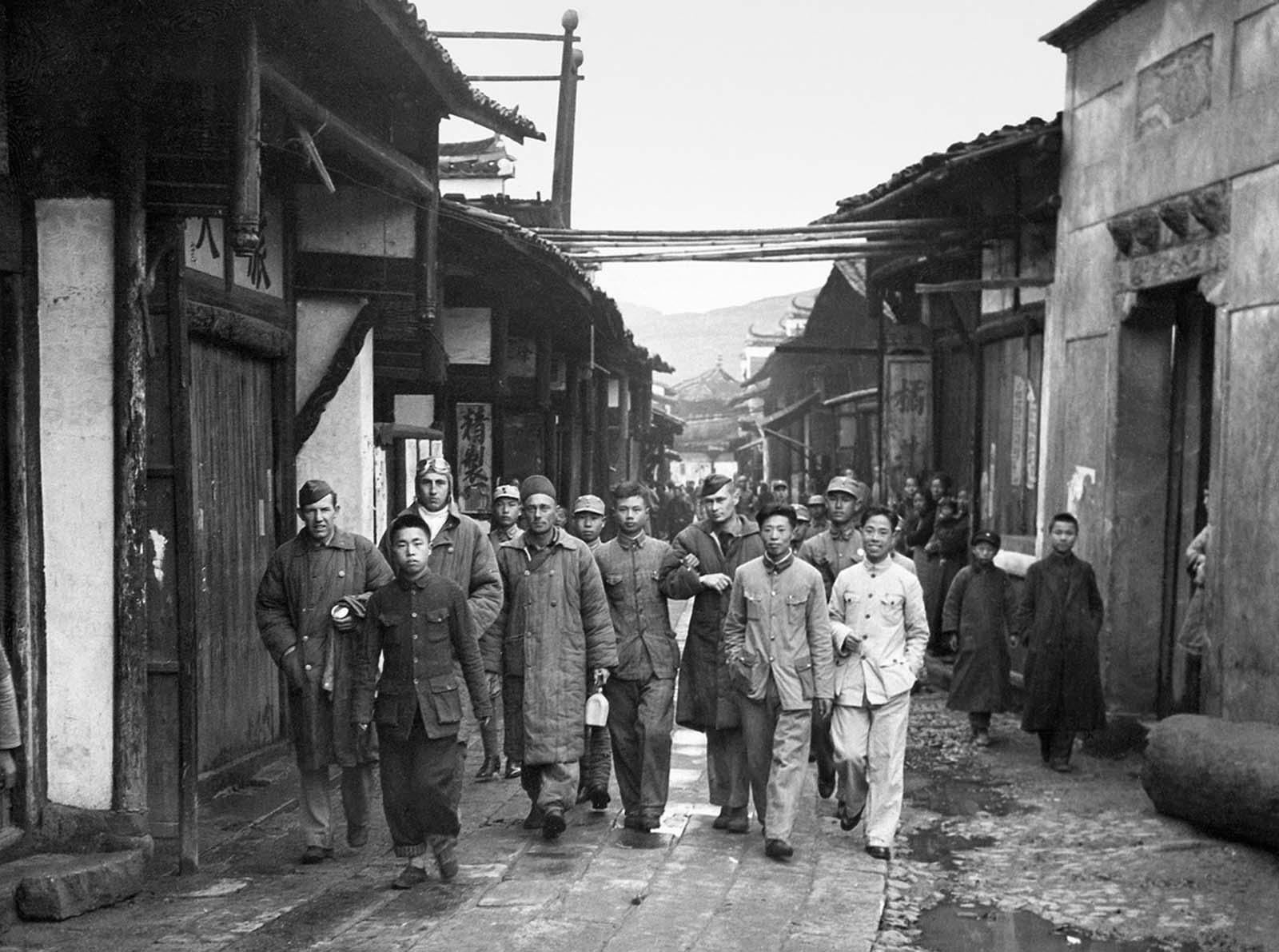 Four unidentified Doolittle Raid crewmen, who bailed out over China from Aircraft #14, are escorted in a Chinese village before being reunited with other airmen in April of 1942. Most of the crew members made it to China, either crash landing, or bailing out over land. The assistance given by the Chinese to the airmen spurred the Japanese Imperial Army to carry out a retaliatory action called the Zhejiang-Jiangxi Campaign -- over the course of four months, entire villages were destroyed, and an estimated 250,000 Chinese civilians were killed.