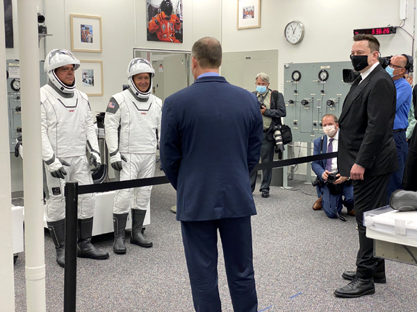 Demo-2 astronauts Bob Behnken and Doug Hurley confer with NASA Administrator Jim Bridenstine and SpaceX founder Elon Musk inside the Neil Armstrong Operations and Checkout Building at the Kennedy Space Center in Florida...on May 27, 2020.